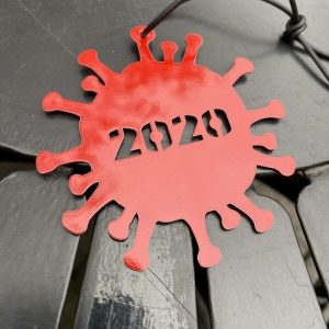 Image of a red Christmas ornament shaped like a virus, with 2020 stenciled in the center
