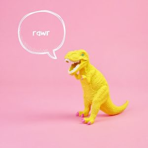 """yellow T-rex toy on a bubblegum pink background. There is a speech bubble coming from the dinosaur's mouth that reads """"rawr"""" in hand-written lettering."""